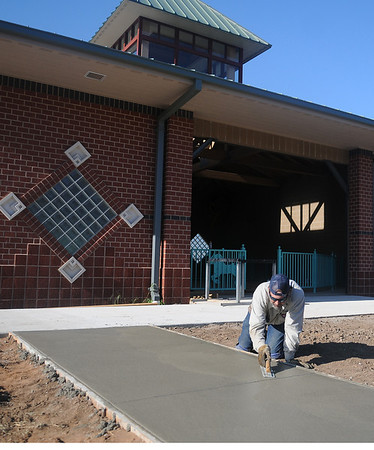 Tim Schultz, with the City of Enid Parks & Recreation concrete team, smooths a new sidewalk section near the Kiwanis Park carousel building Thursday, Oct. 10, 2013. After all of the concrete work has been completed, construction will begin on the amusement ride area at Meadowlake Park. (Staff Photo by BONNIE VCULEK)