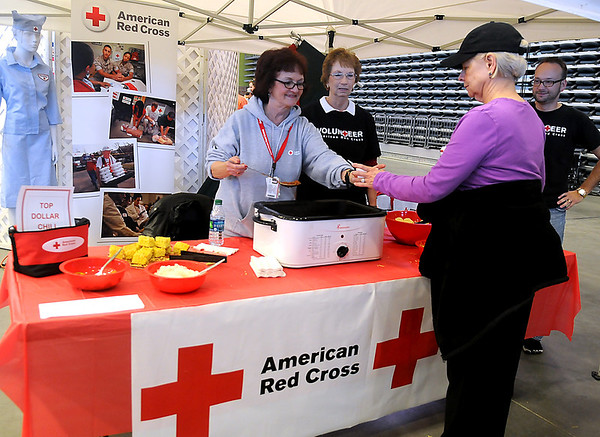 Rose Cohlmia, Janice Taber and Jay Sharp take turns serving the American Red Cross first place chili during the 26th annual United Way Chili Cookoff at the Enid Event Center Friday, Oct. 25, 2013. (Staff Photo by BONNIE VCULEK)