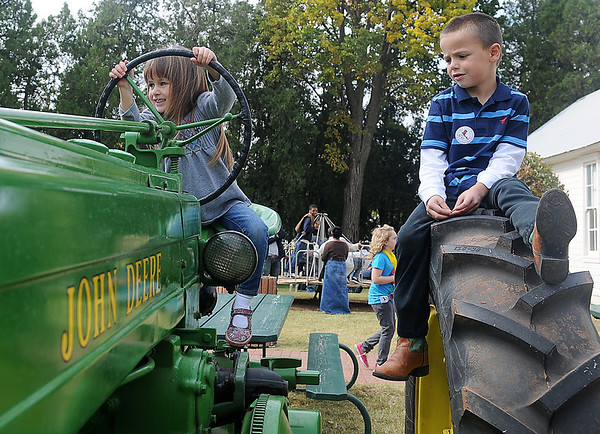 Sophia and Conner Harris relax on an antique John Deere tractor during Family Farm Day at the Cherokee Strip Regional Heritage Center and Humphrey Heritage Village Saturday, Oct. 26, 2013. (Staff Photo by BONNIE VCULEK)