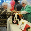 A Ward Petroleum employee (right) dons scrubs in the Ward Hospital chili booth as they assist their clients with a bowl of chili with all the fixin's during the 26th annual United Way Chili Cookoff at the Enid Event Center Friday, Oct. 25, 2013. (Staff Photo by BONNIE VCULEK)