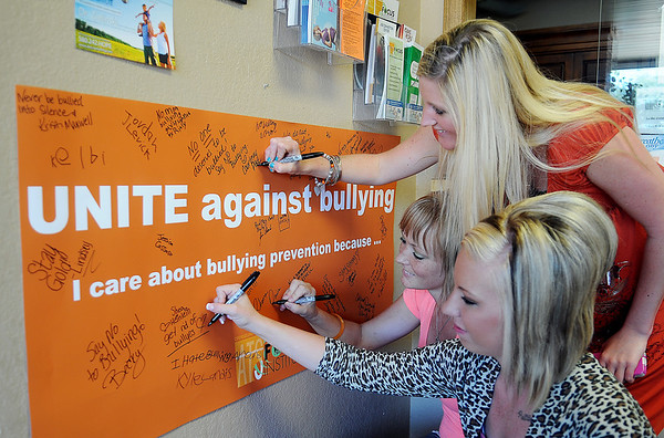"Allison Sherrill, Rhema Davis and Courtney Pike sign the ""UNITE against bullying"" banner at Associated Therapeutic Services Counseling-Focus Institute Wednesday, Oct. 9, 2013. The accredited Enid business, who helped sponsor Unity Day at Waller Middle School, specializes in outpatient treatment; alcohol and other drugs/addictions for adults and outpatient treatment: mental health for children, adolescents and adults. (Staff Photo by BONNIE VCULEK)"