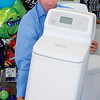 Bob Perry holds one of the smaller Ecowater System units available at Advanced Water Solutions in Enid. The company celebrated its 50th anniversary Oct. 22, 2013. (Staff Photo by BONNIE VCULEK)