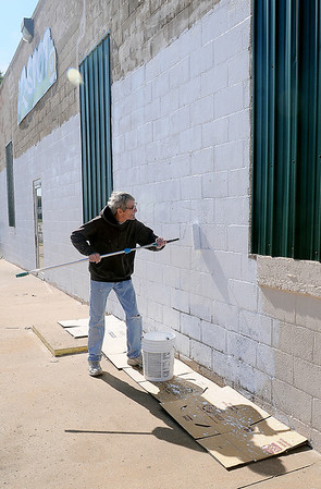 David Himes rolls a coat of primer on the east exterior wall at Q-Spot Thursday, Oct. 24, 2013. In spite of the cooler temperatures, Himes, who owns the business, and his wife, Suzy, braved the elements hoping to finish the painting before rain and freezing weather arrive. (Staff Photo by BONNIE VCULEK)