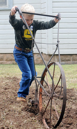 Colton Steinert, 6, learns how to cultivate a piece of ground the old-fashioned way during Family Farm Day at the Cherokee Strip Regional Heritage Center and Humphrey Heritage Village Saturday, Oct. 26, 2013. (Staff Photo by BONNIE VCULEK)
