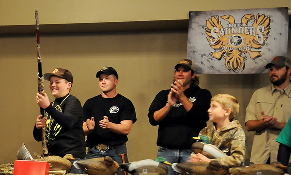 As duck calling competitors applaud, Payton Meyer (left) smiles as he receives a new Winchester SXP Pump Shotgun for placing first in the youth division at the Ducks Unlimited Calling Contest at Oakwood Mall Saturday, Oct. 5, 2013. Glen Niebaum (back center) won the adult division. (Staff Photo by BONNIE VCULEK)