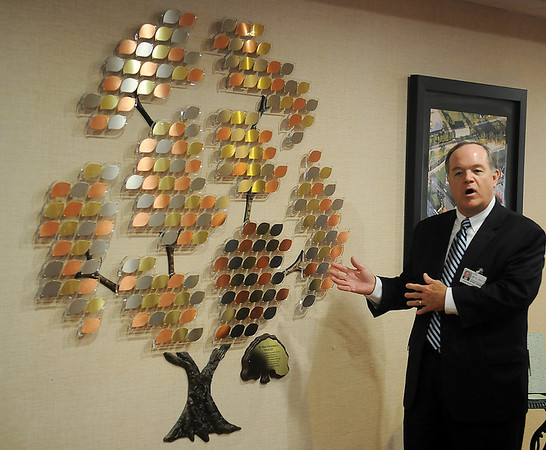 Stan Tatum, CEO of St. Mary's Regional Medical Center, discusses biblical references to the Tree of Life during a reception commemorating long time volunteer, Wanda Cook, on Wednesday, Oct. 2, 2013. St. Mary's Volunteers purchased the art with endowment funds provided by Cook in 2013. Funds generated from memoriam gifts will be used for future projects and scholarships awarded through the volunteer program at St. Mary's. (Staff Photo by BONNIE VCULEK)