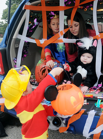 A toddler offers candy to a trick-or-treater during Trunk or Treat at Oakwood Bowl Saturday, Oct. 26, 2013. Several churches and Oakwood Mall are sponsoring safe trick-or-treat locations for children and young adults Halloween night. (Staff Photo by BONNIE VCULEK)