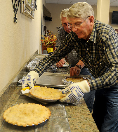 Clif Buckminster (front) and Verlin Koehn place pies onto cooling racks as Grace Mennonite Church members bake a variety of homemade pies Thursday, Oct. 31, 2013, for the Mennonite Relief Sale Friday-Saturday at the Chisholm Trail Expo Center. Proceeds from the two-day event support disaster relief around the world. (Staff Photo by BONNIE VCULEK)