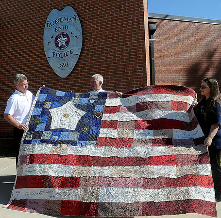 Enid Fire Chief Joe Jackson, Enid Police Chief Brian O'Rourke and 911 Dispatcher April Lucas admire the queen-size quilt designed by Lucas outside the Enid Police Department Wednesday, Oct. 23, 2013. The quilt will be raffled off during the SAS Softball Tournament at Kellet Ballpark this weekend. Chances for the quilt are $2 each and maybe purchased during the tournament or at the Enid Police Department. (Staff Photo by BONNIE VCULEK)