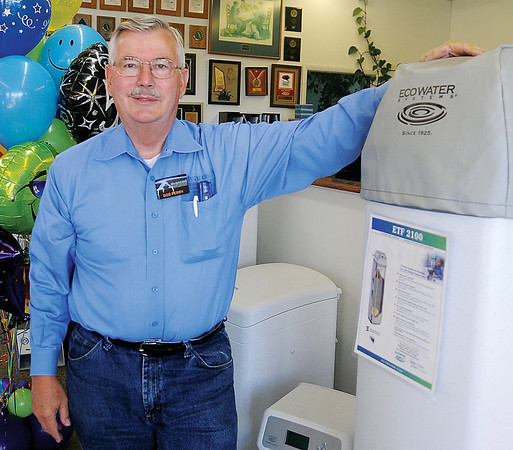 Bob Perry pauses near several Ecowater system units during an interview at 1509 S. Van Buren Thursday, Oct. 24, 2013. Perry began Advanced Water Solutions in Enid 50 years ago. (Staff Photo by BONNIE VCULEK)
