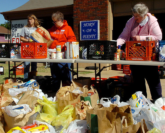 Volunteers sort through donated food items Sunday during the fall Horn of Plenty food drive. (Staff Photo by BILLY HEFTON)