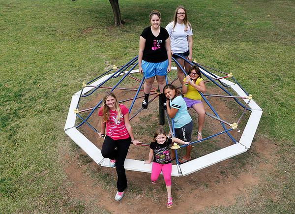 Shayla Kephart, Serita Kephart, Siena Kephart, Chelsea Schulz, Cheyanna Kephart and Tabitha Schulz on the merry-go-round at the Carmen City Park Sunday. The town of Carmen has received and anonymous donation to purchase the first new equipment for the park since the 1920's. (Staff Photo by BILLY HEFTON)
