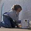 Suzy Himes kneels as she applies primer to the exterior at Q-Spot Thursday, Oct. 24, 2013. Himes and her husband, David, hope to finish the painting before rain and freezing temperatures arrive. (Staff Photo by BONNIE VCULEK)