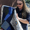 April Lucas unfolds a queen-size quilt that will be raffled off at the SAS Tournament Saturday, Oct. 26, 2013. Lucas, who began quilting a year ago, designed the First Responders quilt which features department insignias and signatures. Chances for the quilt are $2 each and may be purchased during the tournament at Kellet Ballpark or Enid Police Department. (Staff Photo by BONNIE VCULEK)