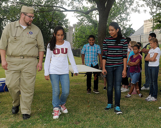 Cherokee Strip Regional Heritage Center education director, Cody Jolliff (left) barks commands to Garfield Elementary School students as they learn how to lift and transport a classmate on a stretcher during a Civil Defense Youth Corp at Government Springs Park Thursday, Oct. 3, 2013. (Staff Photo by BONNIE VCULEK)