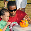 T.K. Slaughter paints a pumpkin with his dad, 1st Lt. Kevin Slaughter, Tuesday during the annual Fall Fest at Vance Air Force Base. (Staff Photo by BILLY HEFTON)