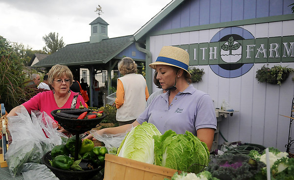Charity Beckner (right) assists customers with their vegetable purchases at Faith Farm Tuesday, Oct. 29, 2013. (Staff Photo by BONNIE VCULEK)