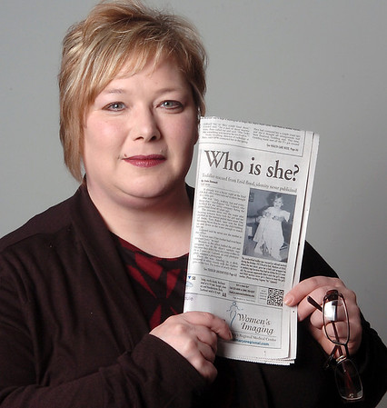 """Carlena Freelove-Otwell holds a copy of The Enid News and Eagle Sunday article """"Who is she?"""" by staff reporter Dale Denwalt during a portrait of her Wednesday, Oct. 16, 2013. Freelove-Otwell, who was the 2-year-old toddler rescued during the Enid flood in October 1973, received a call from a relative in Fairview after the article ran. She and her mother, Vickie Otwell, were swept into Boggy Creek near the old OG&E building before railroad workers rescued the little girl from the raging water. (Staff Photo by BONNIE VCULEK)"""