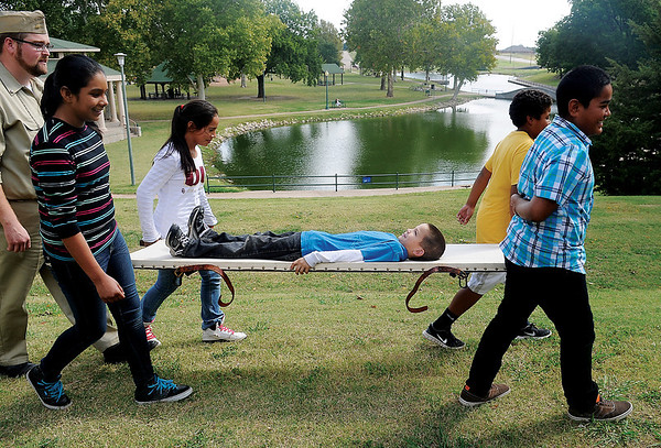 Cody Jolliff (far left), education director at the Cherokee Strip Regional Heritage Center, gives commands to Garfield Elementary School fifth-grade students as they use a stretcher to carry their classmate, Roger Zamarron, during a Civil Defense Youth Corp class at Government Springs Park Thursday, Oct. 3, 2013. (Staff Photo BONNIE VCULEK)