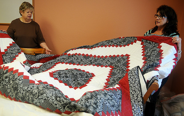 Becky Claborn (left) and Bev Ediger admire the workmanship in a 99 x 99 red, white and black stepping stones log cabin pattern quilt top by Henry and Clarabelle Buller, quilted by Friendship Quilters, at Grace Mennonite Church Thursday, Oct. 31, 2013. During the Oklahoma Mennonite Relief Sale this weekend, hundreds of quilts will be auctioned, raising funds for disaster relief around the world. (Staff Photo by BONNIE VCULEK)