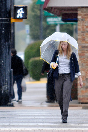 A woman walks with an umbrella as she crosses Grand Avenue through the rain Friday. (Staff Photo by BILLY HEFTON)