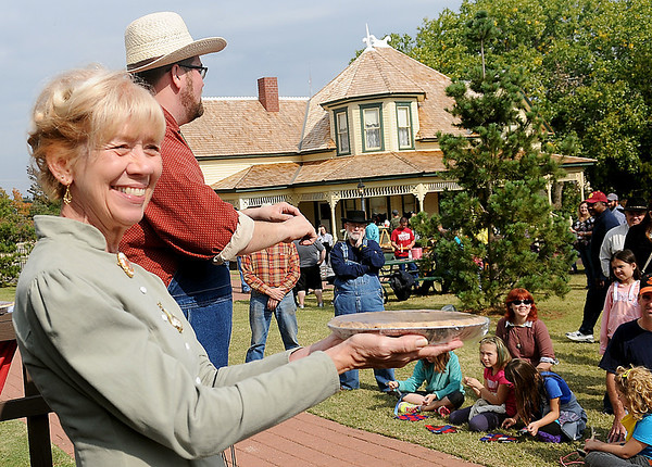 Mary McDonald holds her homemade pecan pie as Cody Jolliff accepts bids at the annual Turkey Creek School pie auction during Family Farm Day at the Cherokee Strip Regional Heritage Center's Humphrey Heritage Village Saturday, Oct. 26, 2013. (Staff Photo by BONNIE VCULEK)