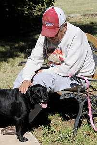 Bella, a new resident dog from the Enid SPCA, visits with an Enid Senior Center client on her first afternoon at the facility Wednesday, Oct. 15, 2014. (Staff Photo by BONNIE VCULEK)
