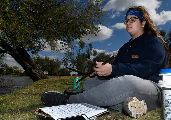 Faith Crum practices drums for a scholarship audition while fishing at Meadowlake Park Thursday October 20, 2016. (Billy Hefton / Enid News & Eagle)