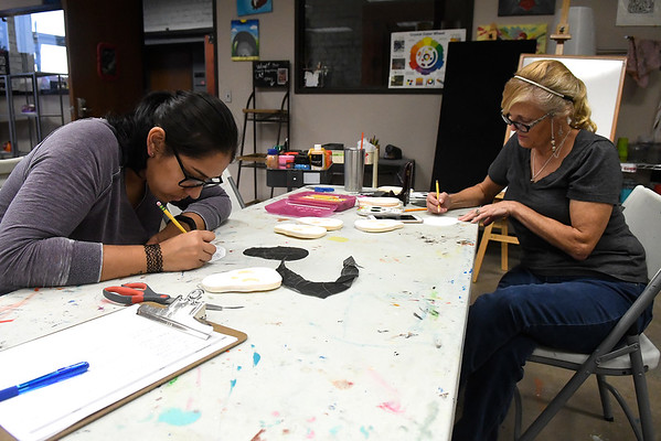 Gabriela Poston (left) and Lori Hill sketch designs for sugar skulls at Creative Arts Enid Tuesday October 25, 2016. (Billy Hefton / Enid News & Eagle)