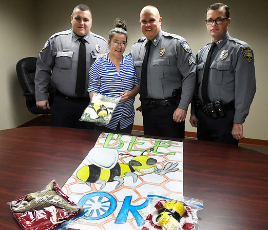 "Enid police officers, Officer James McFadden, Sgt. Jason Priest and Officer Cody Smith, with Terry Cross from the Mabel Bassett Correctional Center Thursday October 13, 2016. Cross presented the EPD with crocheted items from the ""Bee OK"" project at the M.B.C.C. that will be given to children. (Billy Hefton / Enid News & Eagle)"