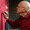 Bert Clampitt, who attended Adams Elementary from 1936-1940, signs his name to a poster during the 100th birthday party from the school Thursday October 27, 2016. (Billy Hefton / Enid News & Eagle)