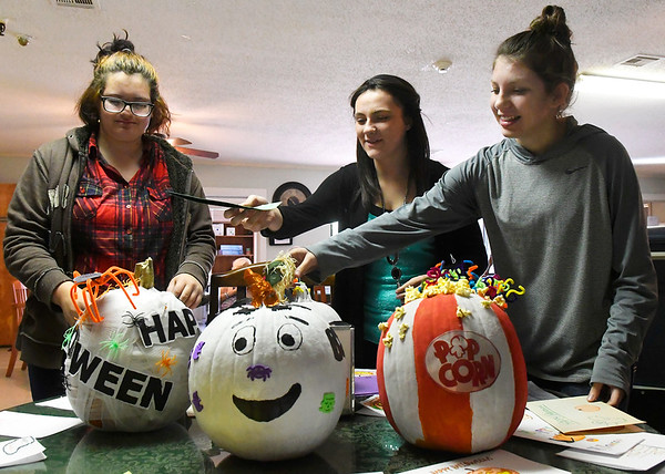 Lincoln Academy students, (left to right) Mackenzie Hicks, Desiree Figurelli and Aubriana Thomas, arrange Halloween pumpkins and cards that students at Lincoln Academy made for the residents at Kenwood Manor. (Billy Hefton / Enid News & Eagle)