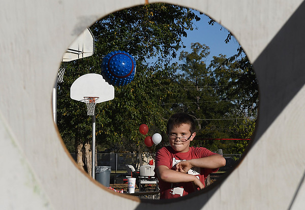 Blake Freeman throws a football at a target during Adams Elementary's 100th birthday party Thursday October 27, 2016. (Billy Hefton / Enid News & Eagle)
