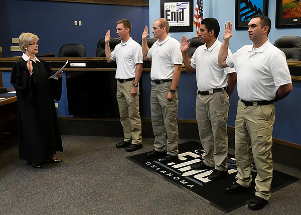 Enid Municipal Judge Linda Pickens swears in the newest Enid police officers, Andrew Ash, Austin Lenamond, Ryan Rios and Bradley Davis Thursday October 5, 2017. (Billy Hefton / Enid News & Eagle)
