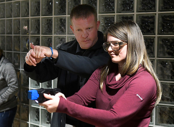 Det. Greg Liebl instructs Kelsey Elliott in the use of a tazer during the Enid Police Department's Citizens Police Academy Tuesday October 30, 2018. (Billy Hefton / Enid News & Eagle)
