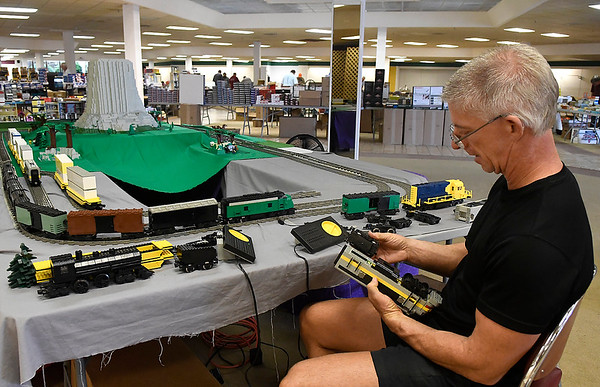 Barry Chandler, from Oklahoma City, works on an engine of his Lego train display at the Cherokee Strip Model Railroad Association Trainfest Saturday, October 5, 2019 inside Oakwood Mall. (Billy Hefton / Enid News & Eagle)