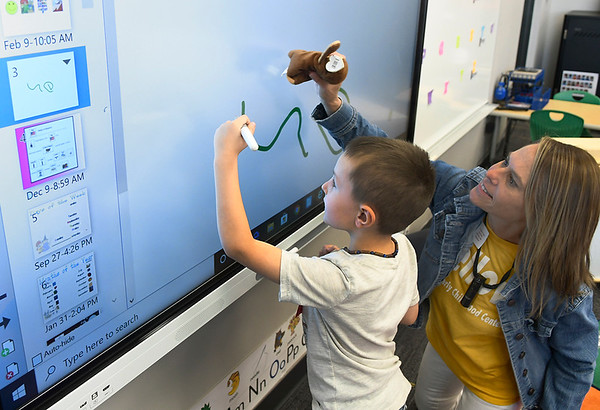 Amy Reed works with Declan Peterson on the smart board in the gold classroom during the first day of class at the Fowler Early Childhood Center at NWOSU Monday, October 21, 2019. (Billy Hefton / Enid News & Eagle)