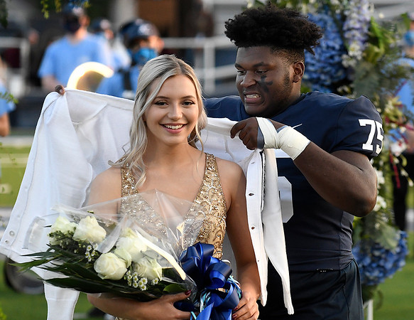 C.J. Adams carefully places the sweater on homecoming queen, Sydney Quarles, during ceremonies Friday, October 9, 2020. (Billy Hefton / Enid News & Eagle)