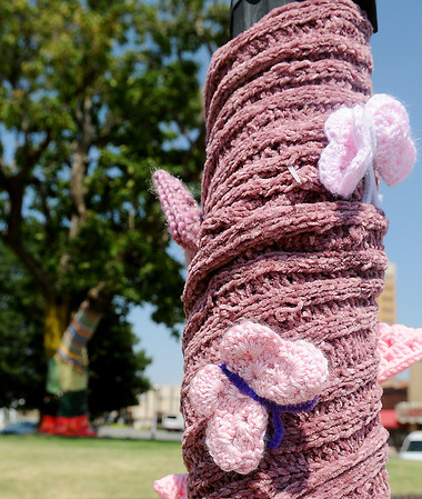 Crocheted butterflies appear on a light pole wrapping on the downtown square as Yarnover Enid enthusiasts hang colorful items Friday, Sept. 6, 2013. (Staff Photo by BONNIE VCULEK)