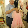 Rev. Jerry Galbreath hangs up one of the small dresses for children inside the wedding attire rooms at University Place Christian Church Wednesday, Sept. 4, 2013. (Staff Photo by BONNIE VCULEK)