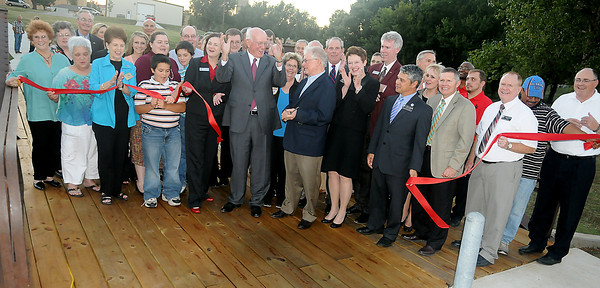 Dignitaries and guests react as the ribbon is cut at the NOC/NWOSU Bridge and Trail dedication Thursday, Sept. 26, 2013. The bridge and trail are symbolic of the commitment that both colleges have made to assist students with their concurrent higher education opportunities in Enid. (Staff Photo by BONNIE VCULEK)