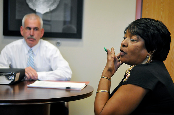 Enid police chief, Brian O'Rourke, looks on as Yvetta Hicks describes where her son, Tramon Johnson, was shot when he was murdered at the Holiday Motel in 1997. (Staff Photo by BILLY HEFTON)