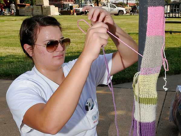Meredith Donaldson sews knitted scarfs to a lamp post around the courthouse square Thursday during the Yarnover Enid event. (Staff Photo by BILLY HEFTON)