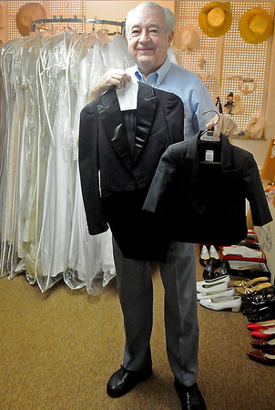 Rev. Jerry Galbreath holds two of the smallest tuxedos that University Place Christian Church has in their wedding attire inventory Wednesday, Sept. 4, 2013. The church offers simply beautiful weddings to couples for reasonable prices. (Staff Photo by BONNIE VCULEK)