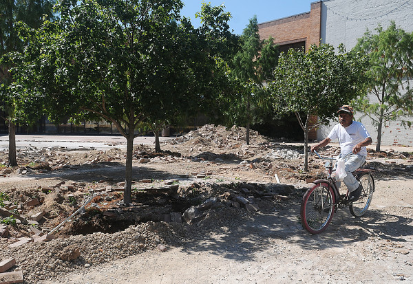 Gustavo Corona rides his bicycle past the Cherokee Strip Conference Center courtyard Wednesday, Sept. 25, 2013. Trees and landscaping bricks are being removed for the construction of the new downtown hotel. (Staff Photo by BONNIE VCULEK)