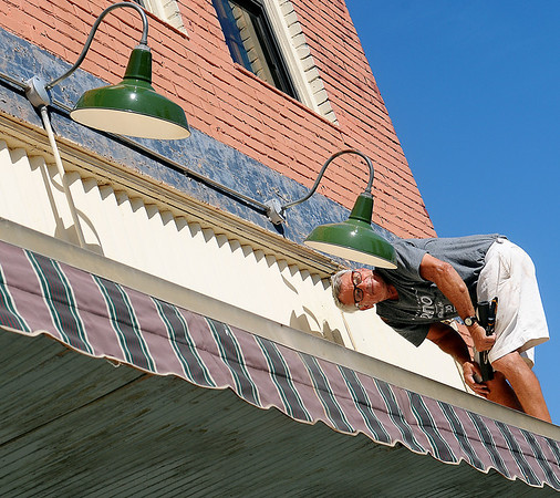 Dan Gaston, a maintenance volunteer for Grace World Outreach Church, checks exterior lighting after repairing a broken cover on one of the three decorative lights above the entrance to K-Life and P.J.s Tuesday, Sept. 3, 2013. (Staff Photo by BONNIE VCULEK)