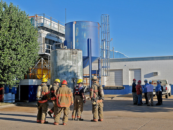AdvancePierre Foods' employees stand outside their facility on E. Pine as additional Enid firefighters prepare to enter the building during an early morning fire Monday, Sept. 23, 2013. (Staff Photo by BONNIE VCULEK)