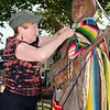 """Susan Southall fastens a blanket around the """"Keeper of the Plains"""" sculpture Thursday during the Yarnover Enid event. (Staff Photo by BILLY HEFTON)"""