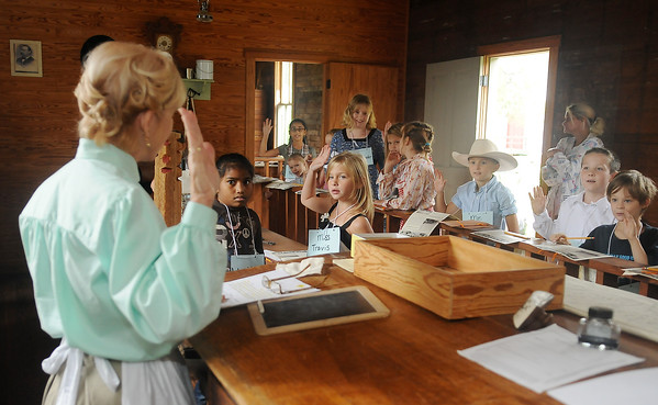 Miss Mary McDonald (left) instructs Garfield Elementary School third grade students as they take an homesteaders' oath inside the U. S. Land Office at Humphrey Heritage Village Friday, Sept. 20, 2013. (Staff Photo by BONNIE VCULEK)