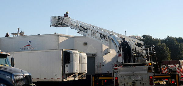 Enid firefighters employ the use of their aerial ladder during a fire at AdvancePierre Foods on E. Pine Monday, Sept. 23, 2013. (Staff Photo by BONNIE VCULEK)